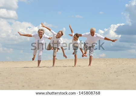 nice brothers with their grandparents walking on the sand in the summer