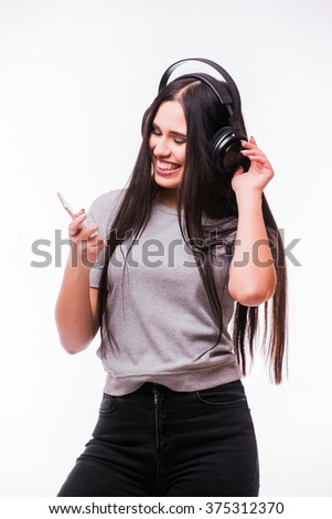 Nice brunette  girl listen dancing to music with headphones with phone in hand on a white background - stock photo