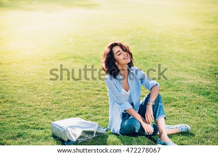 Nice brunette girl with short hair is chilling on grass in park .  She wears white T-shirt, shirt and jeans, shoes. She looks happy and keeps eyes closed.