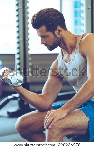 Nice burn in bicep. Side view of confident young handsome man in sportswear exercising with dumbbell at gym - stock photo