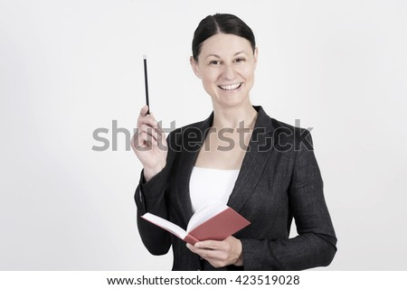 Nice business woman is doing a presentation with pen and notebook in her hand. - stock photo