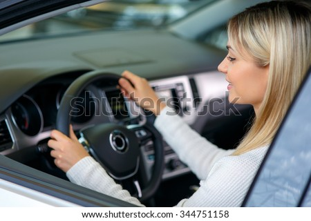 Nice car. Pleasant cheerful delighted woman sitting at the wheel while choosing auto in auto show and going to buy it