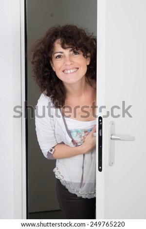 Nice caucasian woman standing near the door to open - stock photo