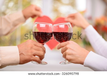 Nice celebration. Close up of glasses in hands of loving adult couple holding them and drinking wine while keeping heart on the background - stock photo