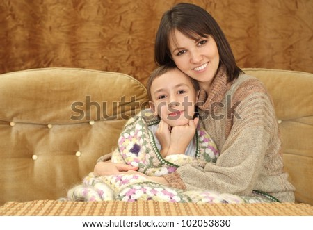 Nice charming Caucasian mama with her son on a brown background