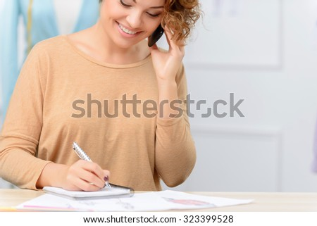 Nice conversation. Pleasant attractive designer holding mobile phone and talking on it while making notes