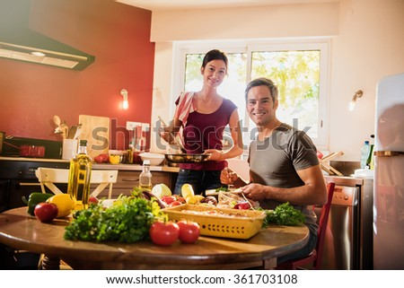 Nice couple looking at camera while cooking fresh vegetables together in a kitchen. The woman in holding the sauce pan while the grey hair man is taking care of the herbs. backlit shot with flare - stock photo