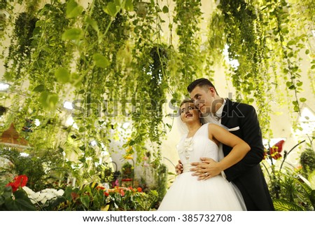 Nice couple near plants - stock photo