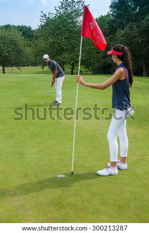 Nice couple playing golf on a green course during a sunny day. The woman is holding the red flag pole while her partner is swinging his club, aiming at the hole They are wearing sportswear outfits