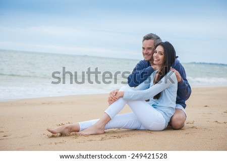 nice couple sitting in the sand in casual clothes, looking at the camera
