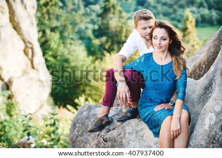 Nice couple sitting on high rock, outdoor. Girl leaning on her boyfriend's knee. Man holding his hand on girls knee. Man looking down and smiling and woman looking aside.