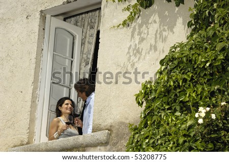 Nice couple talking appearing at a window - stock photo