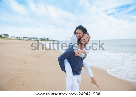 nice couple walking in the sand in casual clothes, looking at the camera - stock photo