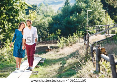 Nice couple walking together, outdoor, in the countryside. Beloved holding hands of each other and smiling. Girl looking down and man looking straight. Full body - stock photo