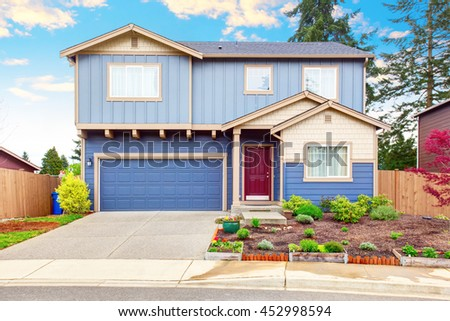 Nice curb appeal of blue house with front garden and garage with driveway  - stock photo