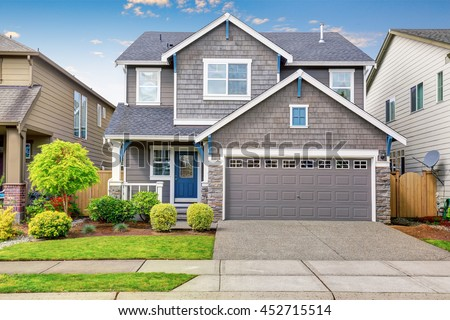 Nice curb appeal of two level house, mocha exterior paint and concrete driveway. View of cozy small porch
