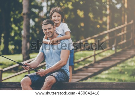 Nice day for fishing! Happy father and son fishing together and smiling while sitting on quayside - stock photo