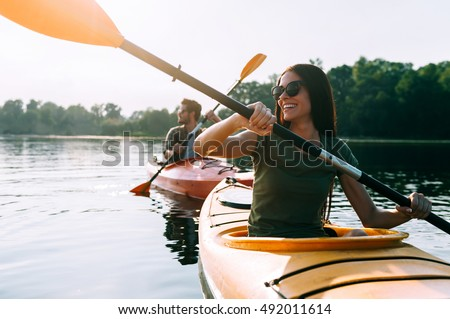 Nice day for kayaking. Beautiful young couple kayaking on lake together and smiling