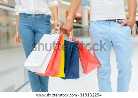 Nice day. Positive cheerful young couple keeping hands together and holding packages while going shopping