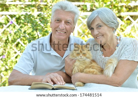 Nice elderly couple with cat in a summer park - stock photo