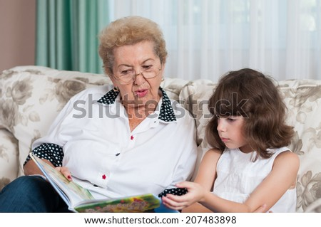Nice elderly woman grandmother reading story to sweet young granddaughter