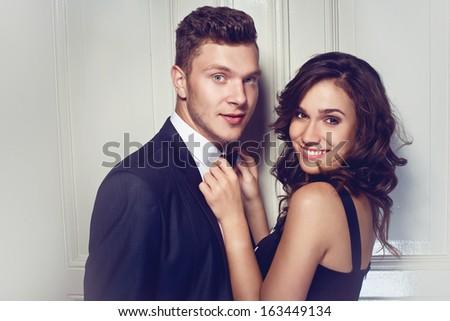 Nice elegant couple next to the door - stock photo