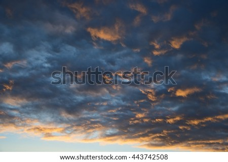 Nice evening sunset with the sun lighiting up the underside of the clouds - stock photo