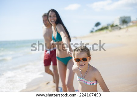 nice family in swimsuit walking on the beach - stock photo