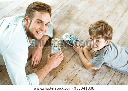 Nice family photo of little boy and his father. Boy and dad playing with cars on wooden floor - stock photo