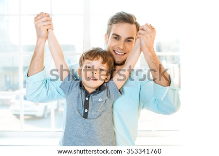 Nice family photo of little boy and his father. Boy and dad smiling and looking at camera. Young man raising his son by arms - stock photo