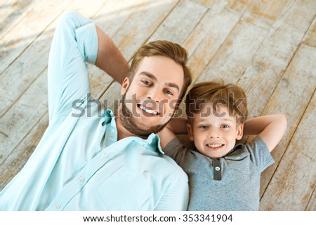 Nice family photo of little boy and his father. Boy and dad smiling and lying on wooden floor - stock photo