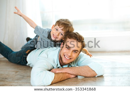 Nice family photo of little boy and his father. Boy and dad smiling and lying on wooden floor. Boy riding piggyback - stock photo