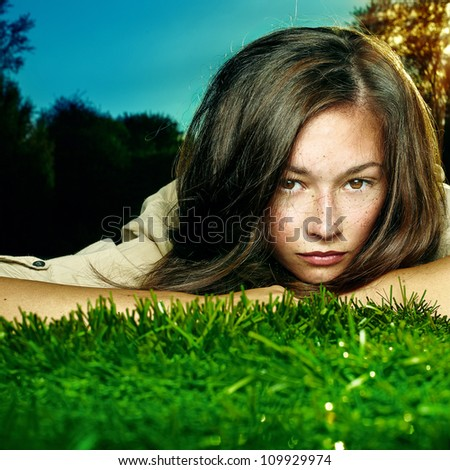 Nice female lying down in the meadow of flowers, pretty girl relaxing outdoor, having fun, happy young lady and spring green nature, harmony and freedom - stock photo