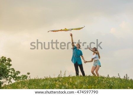 Nice flight of a kite in the form of an eagle with painted feathers in different colors. Strong positive emotions of young couple during the play with a toy.