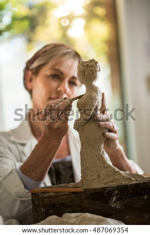 nice forty years old woman who makes sculpture with a lap . she is in her workshop. she is concentrated, she is sculpting a woman with a tool that she is holding in her hand.