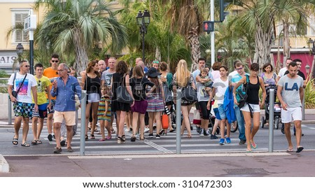 NICE, FRANCE - AUGUST 16, 2015: People crossing Promenade des Anglais street on Nice coast avenue. Nice is 5th most populous city in France and capital of Alpes Maritimes department.