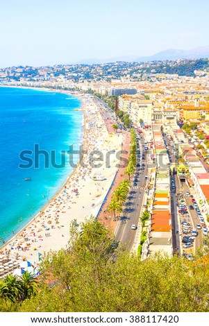 NICE, FRANCE - AUGUST 10, 2012: Tourists enjoy the good weather at the beach in Nice, France. The beach and the waterfront avenue, Promenade des Anglais, are full almost all the year. - stock photo