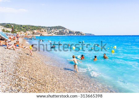 NICE, FRANCE - AUGUST 23: Tourists enjoy the good weather at the beach on August 23, 2015 in Nice, France. The beach and the waterfront avenue, Promenade des Anglais, are full almost all the year. - stock photo