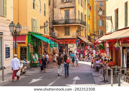 NICE, FRANCE - AUGUST 23, 2014: Tourists in Old City of Nice - fifth most populous and second-largest French city on Mediterranean coast and one of most visited with 4 million tourists every year.