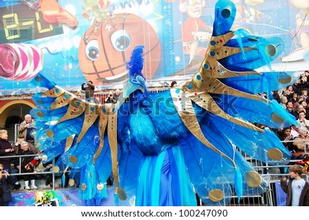 NICE, FRANCE - FEBRUARY 21: Carnival of Nice in French Riviera. This is the main winter event of the Riviera. The artist dressed in the costume of A Fantastic Blue Bird. Nice, France - Feb 21, 2012 - stock photo