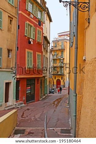 NICE, FRANCE - FEBRUARY 21, 2012: The quiet narrow streets of the old residential neighborhood in the city centre consist of colorful tilted houses, sometimes twisted by vines, on February 21 in Nice.