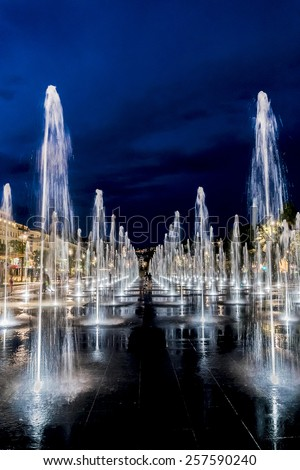 NICE, FRANCE - JULY 7, 2014: Famous Fountain on Place Massena at night. Place Massena - Main Square of the city and it is used for concerts and other events which take place in the city. - stock photo