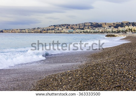 NICE, FRANCE, on JANUARY 7, 2016. A beach and the line of a surf with waves. Embankment in the distance