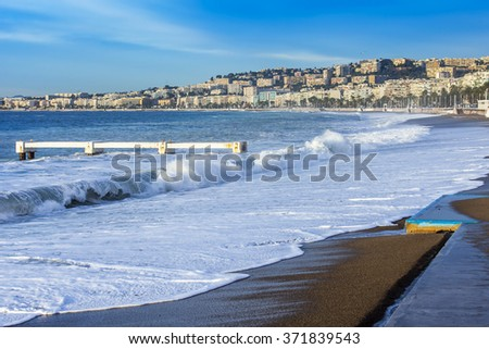 NICE, FRANCE - on JANUARY 8, 2016. View of the line of a surf, wave, beach and Promenade des Anglais Embankment, one of the most beautiful embankments of Europe