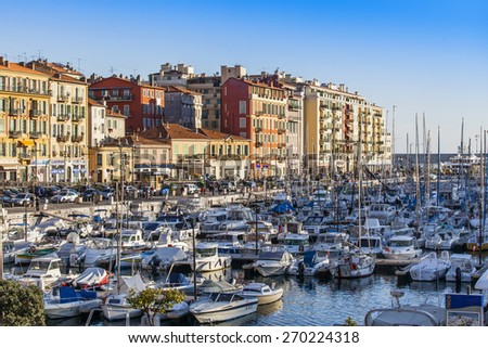 Nice, France, on March 7, 2015. A view of the embankment and the yacht in city port at sunset - stock photo