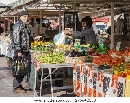 Nice, France, on March 11, 2015. Buyers in the market choose vegetables and fruit - stock photo