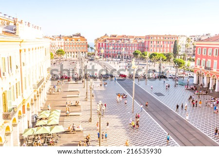 NICE, FRANCE - SEPTEMBER 06, 2014: Tourists walking in the Place Massena in Nice, France. The place is the most famous of the city because of its beauty, shopping options and the carnival. - stock photo