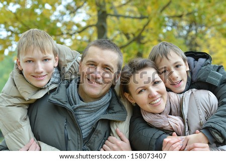 nice friendly family for a walk in the park in autumn