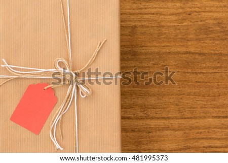 Nice gift wrapped with brown paper and decorated with white ribbons and red