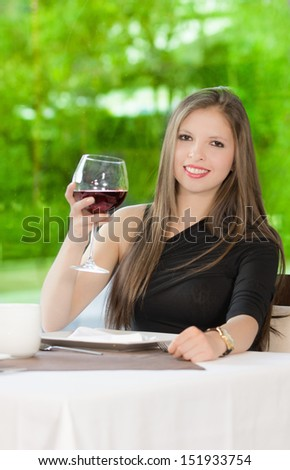 Nice girl and wineglass in a restaurant - stock photo